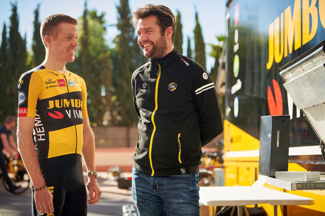 Team Jumbo Visma Sport Diretor Addy Engels smiling while standing beside a Team Jumbo Visma athlete.-1
